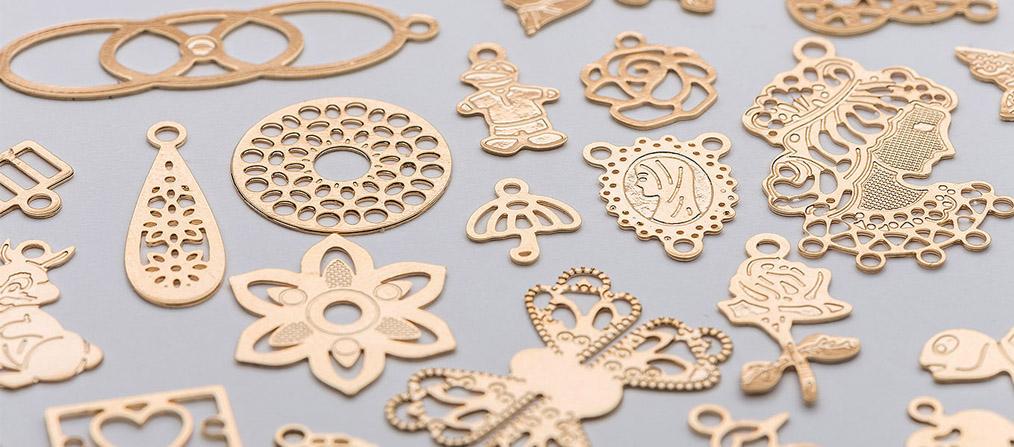 Várias peças fabricadas através do processo de fotocorrosão, com rebaixos, relevos, rendas e desenhos detalhadas, já banhadas a ouro amarelo. Imagem: Roal Acessórios